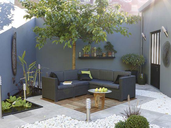 Déco terrasse zen aménagée avec un sol en dalles de bois pour le coin salon de jardin et de galets et carreaux de pierre grise en damier. Le...