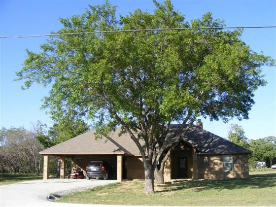 Rustic great family home Stone wood burning fireplace beautifully stained custom cabinets granite kitchen and bathroom counter tops awesome master bath set up walk in closets in all bedrooms large matching 2 car carport open concept carpet in all bedrooms huge tiled flooring nice glass star door for great entrance Must see houses are not close to you but yet your still in town... City sewer and water which is a plus