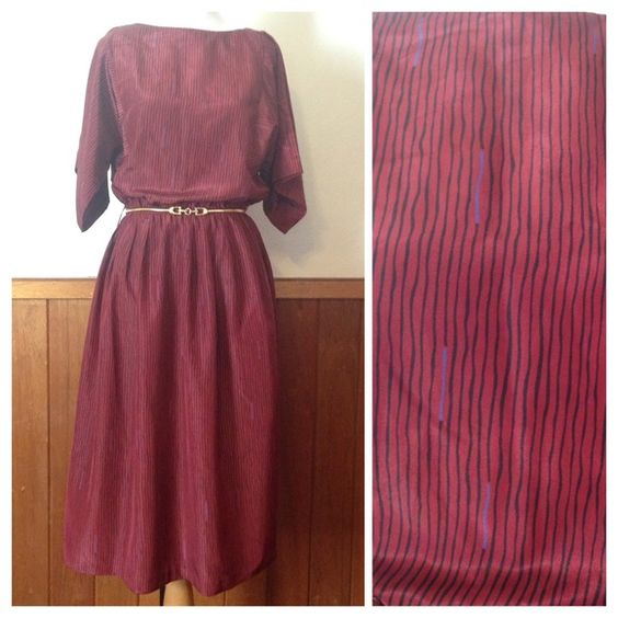 Vintage dress Vintage cranberry colored dress with black and purple. Cinched at the waist so can fit a S/M /L and has unique flare 3/4 sleeves. Great vintage condition. Measurements upon request. Vintage Dresses