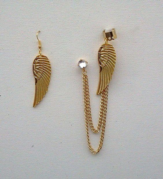 Ear cuff da moda, feito com corrente de metal dourado e pingentes de asas de anjos e ponto de luz cristal na orelha direita. Um acessório super fashion, em evidencia na moda. Também na versão prateada ou ouro velho.