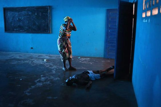 <b>TIME LightBox: How John Moore Covered the Ebola Outbreak</b><br>Umu Fambulle stands over her husband Ibrahim after he staggered and fell, knocking him unconscious in an Ebola ward on Aug. 15, 2014 in Monrovia, Liberia.