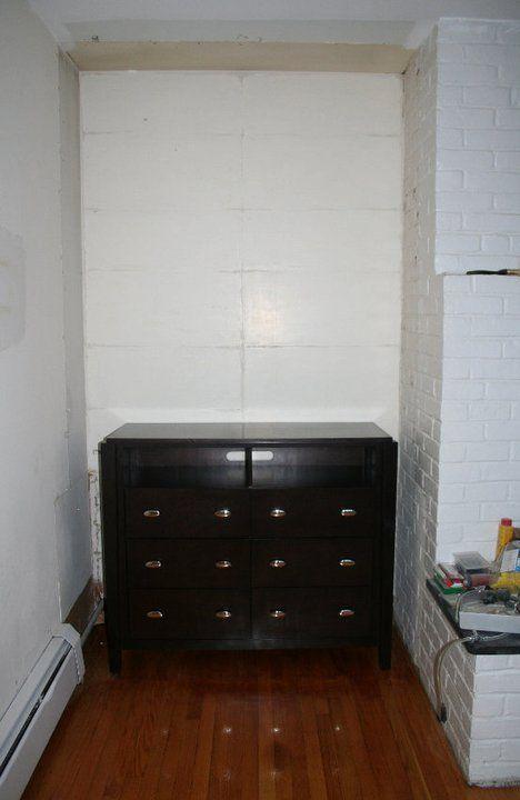 old built in shelves alongside not centered white brick fireplace