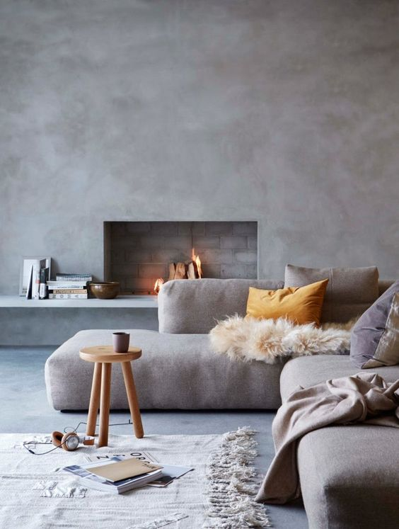 Gray cement wall, low modern sectional, fireplace, gray floor