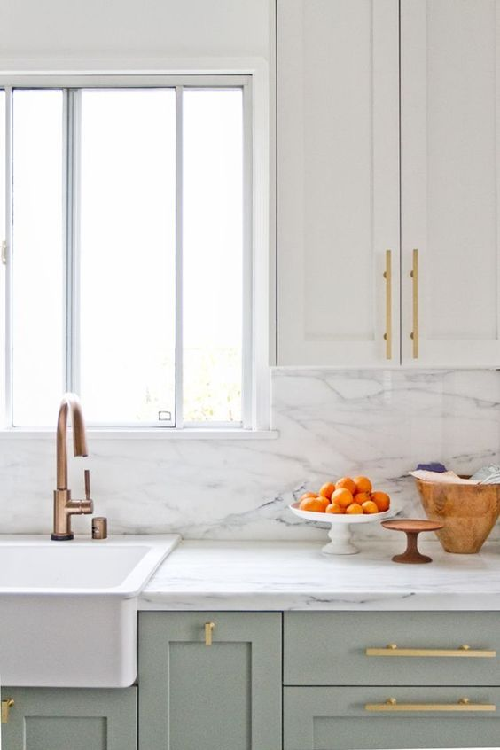 Serene kitchen design with two tone cabinets, marble counters and backsplash, brass hardware, and farm sink. #kitchendesign #kitchendecor #whitekitchen #serene #farmsink #brasshardware