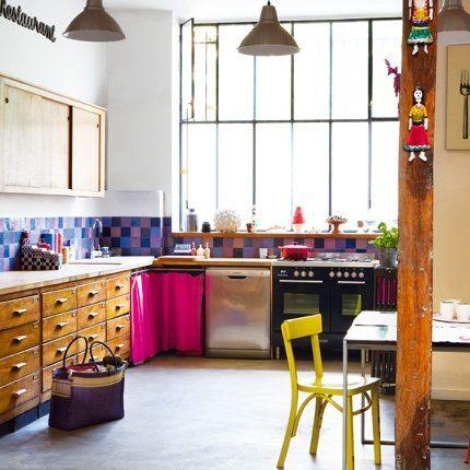 Un meuble en chêne massif occupe tout un mur de la cuisine. Il a été recouvert d'un plan de travail en bois. Pour en souligner l'exceptionnelle longueur, il a été bordé d'une bande de carreaux émaillés multicolores qui se prolonge devant la partie technique, en guise de crédence. Au-dessus, un placard à portes coulissantes et des étagères dans l'angle dissimulées derrière un rideau.