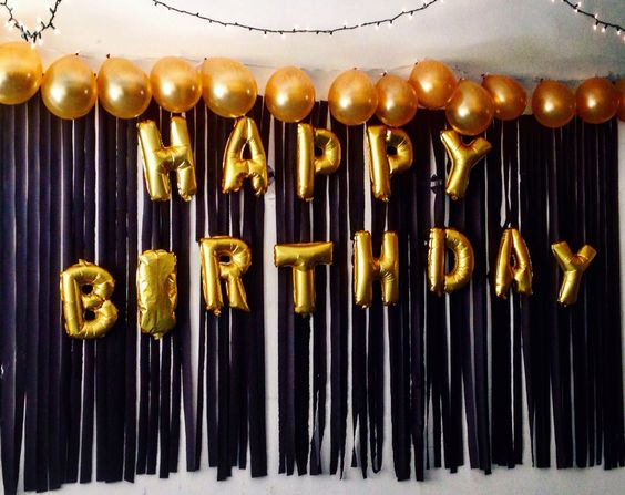 Happy Birthday Balloons taped on a backdrop of black streamers with gold balloons at the top!