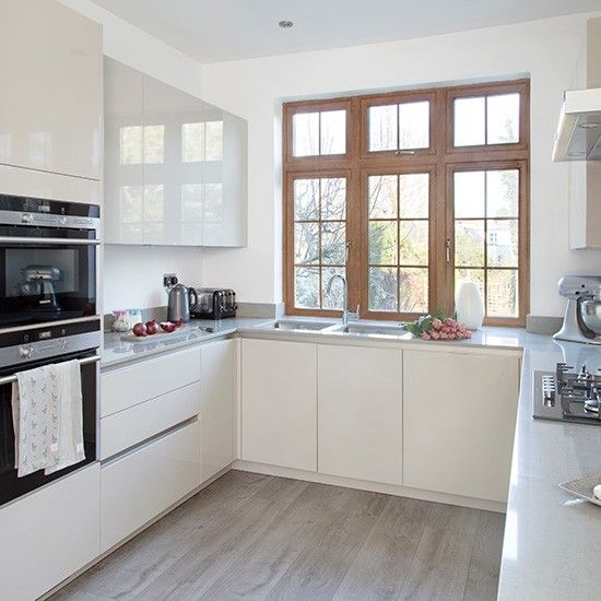 Modern U-shaped kitchen with handleless cabinetry. i like the combination of cream handleless cupboard, light work surface and wood floor