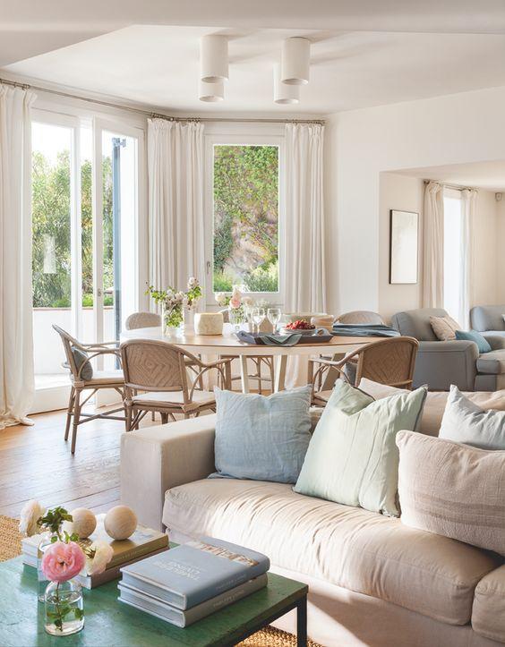 Hacia el comedor. Blanco, crudo y azul son los colores que dominan la decoración. El tablero de la mesa de comedor es de la misma madera que el suelo.