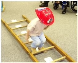 Fire Ladder Jump with Numbers:  We taped the numbers 1-10 between the rungs of a large wooden ladder.  The children then took turns counting and jumping through the rungs of the ladder.  We held hands on either side of the jumping child and gave a boost as necessary so that everyone would be successful regardless of jumping ability.: