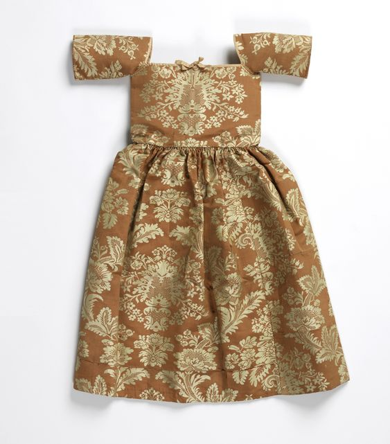 Child's Dress, early 18th century, England Child's dress of coral-colored silk damask with floral pattern in white. Bodice cut square at neck and edged with pink ribbon; elbow length sleeves; full gathered skirt.