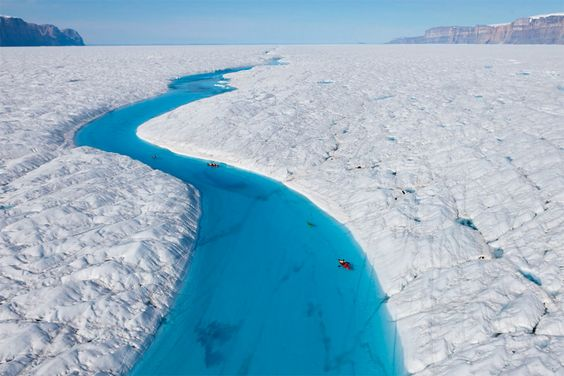 Blue river of Greenland which is surrounded in all direction by white