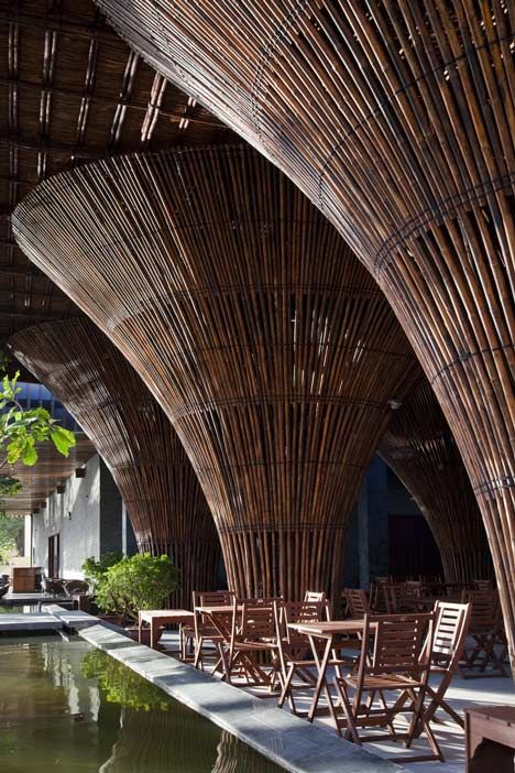 Fifteen conical bamboo columns support the roof of this waterside cafe designed by Vo Trong Nghia Architects at a hotel in central Vietnam. The restaurant does not have any walls, allowing uninterrupted views across the surrounding shallow pools of water, and beyond that towards the neighbouring river and distant mountains.: