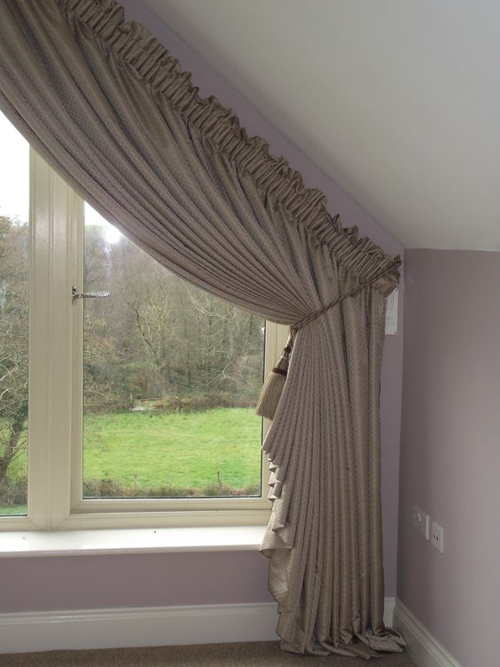 Shaped curtains on a triangular window made by Ger's Curtains & Blinds: