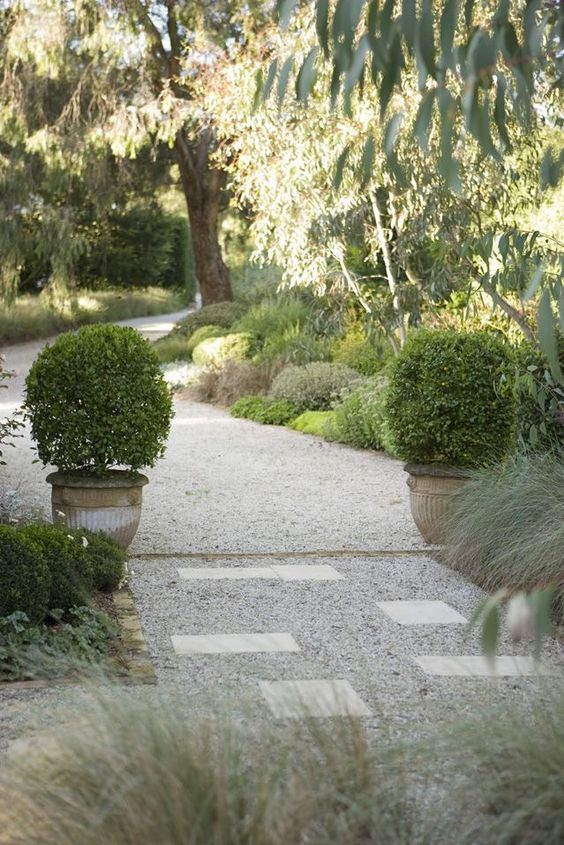 Potted plants frame the beginning of a crushed gravel garden path with a mixed border by Peter Fudge.