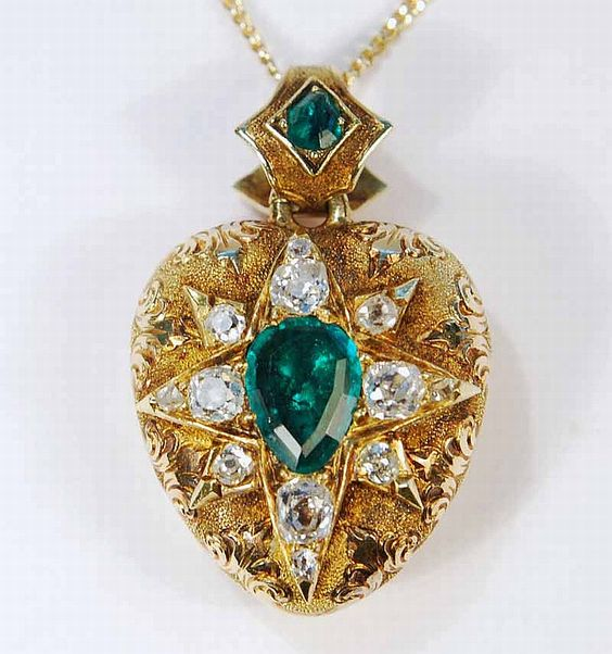 A Victorian emerald and diamond locket pendant set with two emeralds and 12 old cut diamonds.