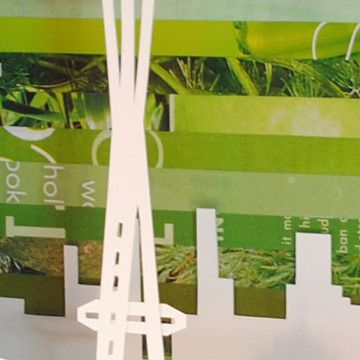 """Space Needle Shadowbox (by Amy Gibson) (2/2) - intricately hand-cut Seattle icon against an emerald-colored collage of discarded pages. Shadowbox is 10"""" x 10"""", frame is 0.75"""" thick and 1.75"""" deep. Can do other city landscapes!"""