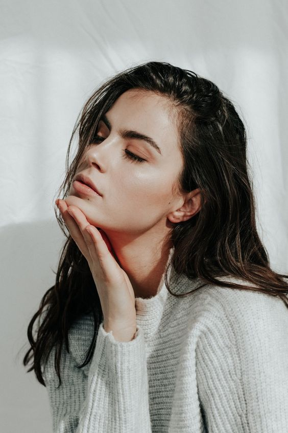 Brunette closing her eyes and with hand on chin.