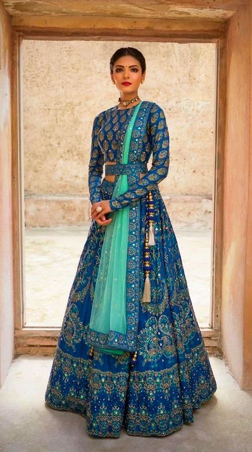 A model displays an enchanting blue silk pearl ethnic designer lehenga with full sleeves and belted blouse. If you want to look different then belted lehengas would be a perfect choice and you can easily hold up your dupatta with the help of a belt. (Image Source: Pic Click) #lehenga #designerlehenga #fullsleevesblouse #beltedblouse #blouse #designerblouse #ethnicwear #designerclothing #clothingdesigner #highfashion #womensclothing #fashion #fashionista #fashionblogger #fashionlover #style