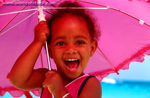 Smiling child....under her umbrella, glaring out the sun at the beach!: