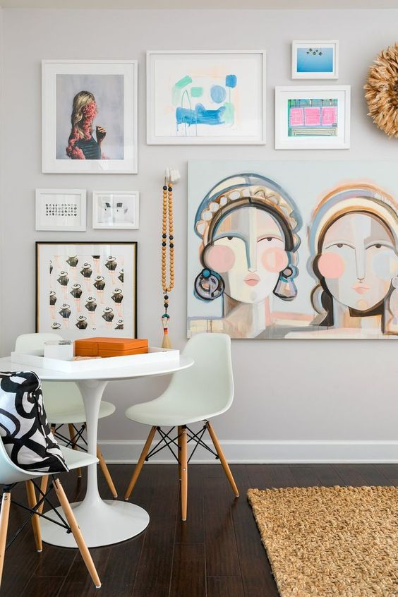 Simple gallery wall behind a white table with prints and 3D objects hanging