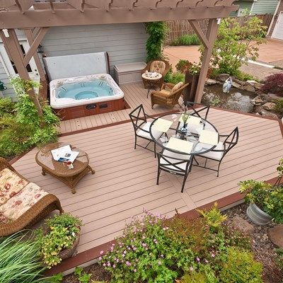 This very small backyard between the house and garage is turned around in a little paradise. We have a small grill area, dining area and a small relaxing area. Space is set aside for a hot tub with a pergola. As an added bonus the homeowner wanted a fishpond with a water feature.