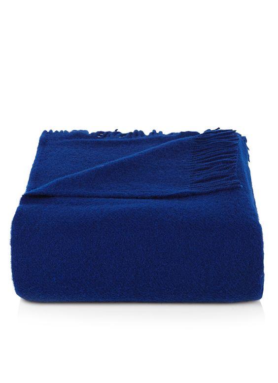 Plaid Vika van Silkeborg, vervaardigd uit een hoge kwaliteit lamswol. Dit marineblauwe model heeft ruime afmetingen en is aan weerszijden voorzien van lange rafels. Ideaal om te draperen op de bank of als decoratie op het bed.