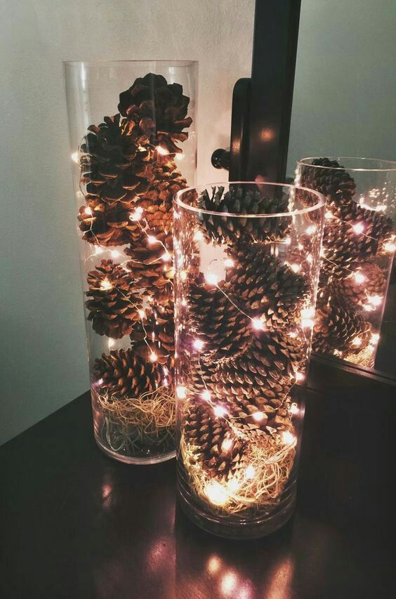 A simple yet festive idea: pinecones and mini lights in clear glass vases!