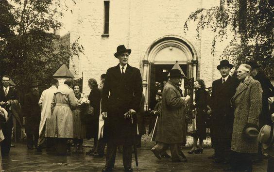 Cartão Postal do Príncipe Gabriel Constantinovich (Gavriil Konstantinovich) em cerca de 1948. Ele está em pé na frente de um grande edifício de pedra vestindo um terno escuro e chapéu. As pessoas estão reunidas na calçada em torno dele.