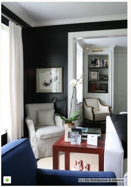 Black walls, white trim. dark floors with white area rugs.