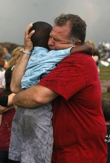 A Teacher hugs a child at Briarwood Elementary in OK after tornado