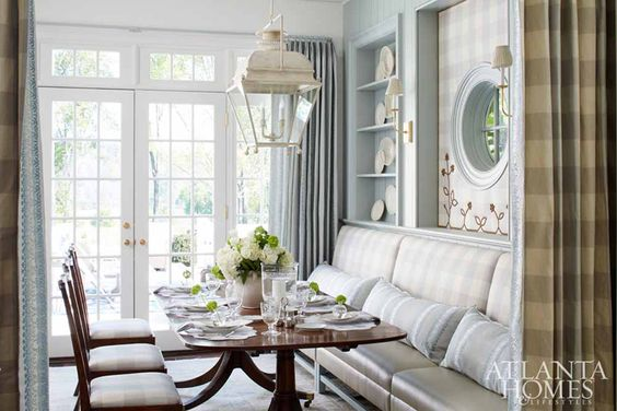 Blue and white #breakfastroom with fabric upholstered wall, brass nailhead trim, and banquette