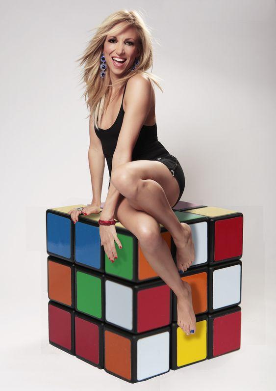 Debbie Gibson sitting on a Rubik's Cube