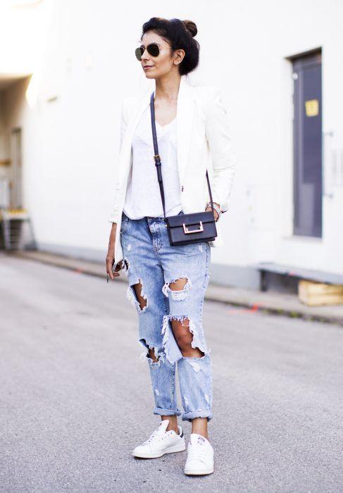 Chica usando pantalones en color azul rasgados, blazer y zapatillas en color…