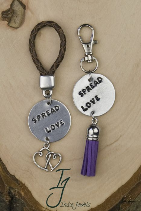 Spread Love sleutelhangers. Links met gevlochten leren lus, aluminium plaatje en bedeltje dubbele hart. Rechts met karabijn sluiting, aluminium plaatje en suede kwastje.