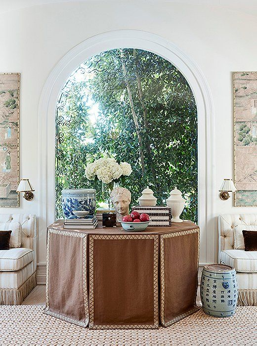 """A skirted table adds a feminine and sophisticated touch to a room,"" says Mark. ""And they're practical—you can stow things out of sight."""