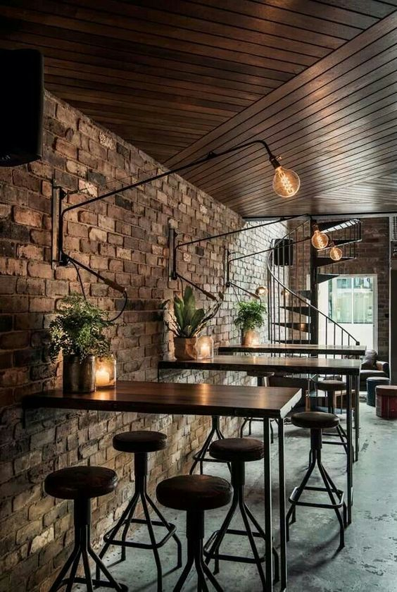 I love the whole set up. Tall wooden table, metal and wood stools, metal container with plant, candle jar, and tall extended lamp
