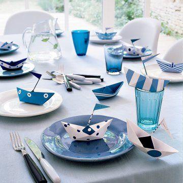 Marque-places comme des bateaux en papier plié bleus et blancs