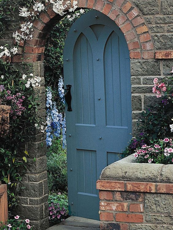 An arched wooden door set in a stone or brick wall is a design classic. Peeling paint and rusting fittings will only add to its charm.