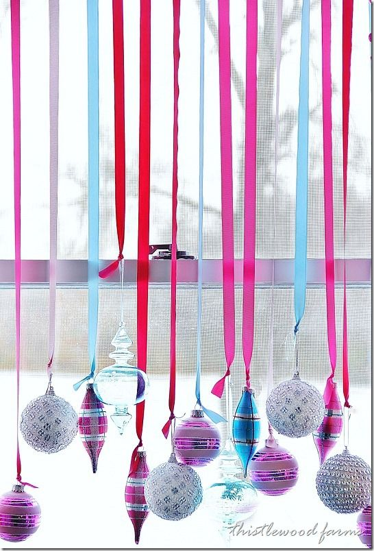 decorate-a-window-with-ornaments... Next year in my window.... By my desk...with command strips and really long silver ribbon