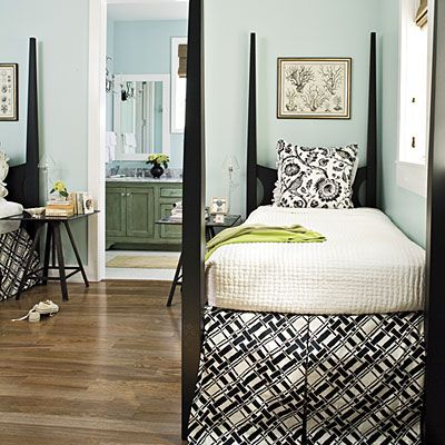 Graphic black-and-white bedding on simple pencil post beds makes a bold statement in an otherwise tranquil room.