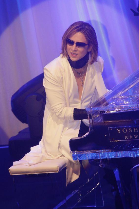 青いライトの中で白いジャケットを着て演奏しているXJAPAN・YOSHIKIの画像