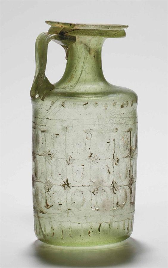 A ROMAN FACET CUT GLASS JUG CIRCA 4TH CENTURY A.D.