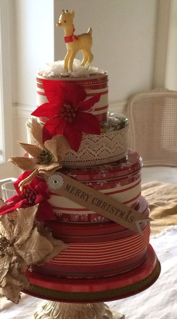 Old cookie tins dressed up and stacked up on a cake for Decorating tins for christmas