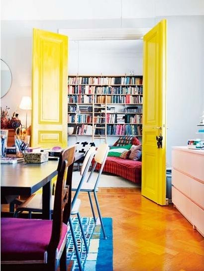 I am in love with the huge yellow doors! And the wall of books back there makes my heart sing. I approve of just about everything in the picture, actually. <3: