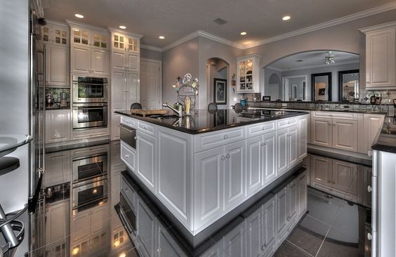 A large kitchen always looks ritzy and this one has large appliances, an oversized island and underlighting to enhance that opinion. Even more, the floors are so shimmery that they actually reflect the entire kitchen back to you.