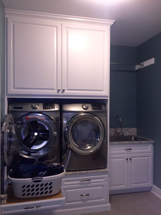 Built in for laundry room.  Great alternative for laundry pedestals.  Laundry room color is Sherwin Williams Moody Blue and backsplash is Cambria Berwyn Quartz.  Build ins were made by Glicks Custom Cabinets.