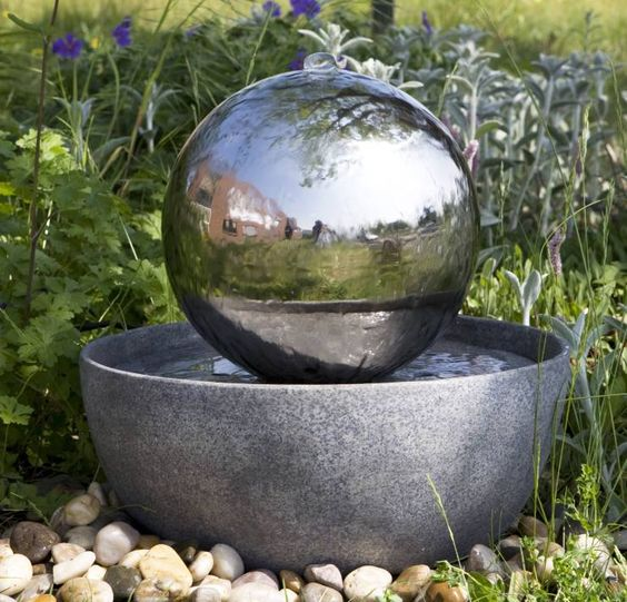 Stainless steel globe on stone water feature