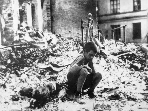 Nine-year-old Ryszard Pajewski sitting in a pile of rubble after a German raid on Warsaw, Poland, Sep 1939