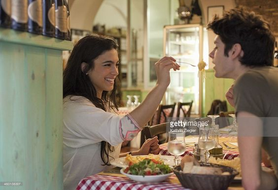 happy young couple eating together in restaurant:
