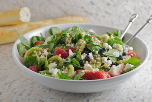 spinach salad with berries, kiwi, and goat cheese.